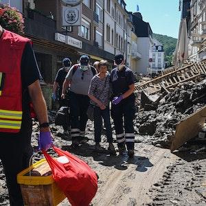 Helfer der Johanniter in Bad Neuenahr-Ahrweiler begleiten nach der Flutkatastrophe eine Seniorin aus ihrer Wohnung.