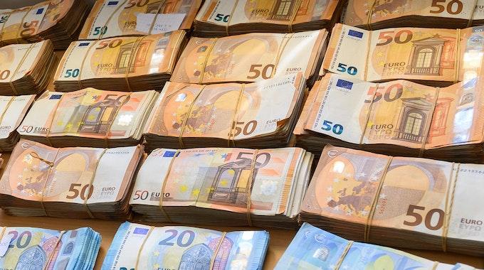 Auf einem Tisch liegen Bündel aus Fünfzig- und Zwanzig-Euro-Scheinen.
