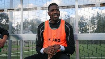 Ex-Gladbacher Mo Idrissou sitz am 10. Oktober 2020 im orangenen Leibchen beim Spiel gegen den Hunfelder SV auf der Ersatzbank beim SC Viktoria Griesheim und lächelt.