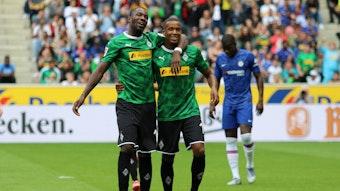 Thuram und Plea laufen Arm in Arm über den grünen Rasen des Fußballplatzes, sie tragen das grüne Gladbach-Trikot.