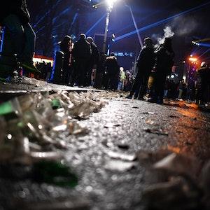 Auf einer Straße vor dem Brandenburger Tor liegen in der Silvesternacht 2017 Glasscherben. Im Hintergrund stehen Menschengruppen.