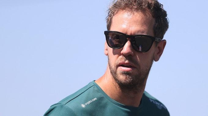 Sebastian Vettel guckt mit Sonnenbrille in die Kamera.
