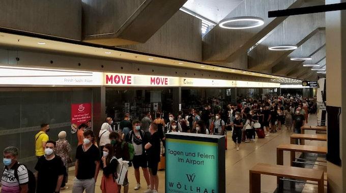Reisende stehen am Flughafen Köln/Bonn Schlange.