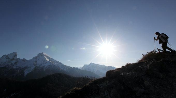 Eine Bergwanderin geht im April 2010 vor der Kulisse des Watzmanns durch die Bergwelt des Berchtesgadener Landes.