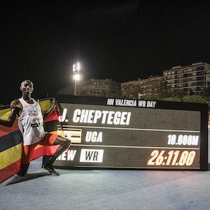 Joshua Cheptegei posiert neben einem Bildschirm mit seinem Weltrekord.