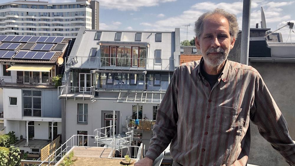 Architekt Gabor Schneider steht auf einem Balkon, der sich noch im Rohbau befindet. Im Hintergrund der Dachgarten und das Wohnhaus.