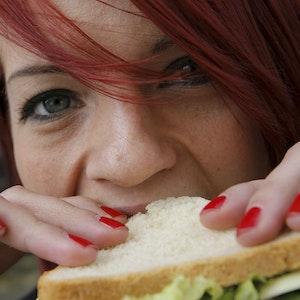 Eine Frau beißt am 28.03.2008 in Berlin in ein Käse-Sandwich.
