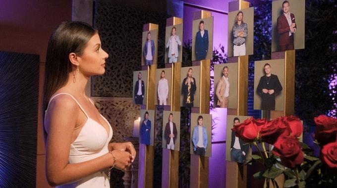 Maxime Herbord, Bachelorette 2021, steht vor Fotos der Kandidaten und überlegt, wem sie eine Rose gibt.