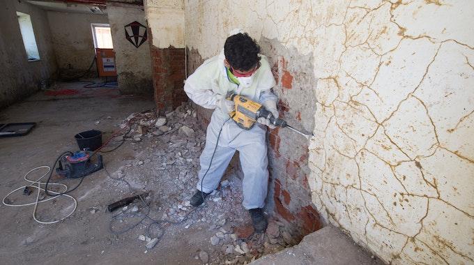 Ein Mann in einem Schutzanzug schlägt am 23. Juni 2016 in Simbach (Bayern) mit einem Bohrhammer Putz von einer Wand.
