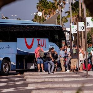 Touristen mit Mundschutz holen ihr Gepäck aus einem Bus auf den Kanarischen Inseln.