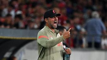 Jürgen Klopp, Trainer des englischen Top-Klubs FC Liverpool, brüllt bei einem Testspiel gegen Hertha BSC in Innsbruck am 29. Juli 2021 Anweisungen auf das Spielfeld. Mit dem rechten Arm gestikuliert er, in der linken Hand hält er derweil eine Getränkeflasche.