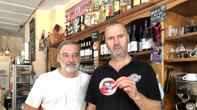 """Rüdiger Nehl und Dieter Niehoff stehen hinter der Theke im Restaurant und halten den """"Jode Lade""""-Sticker in die Kamera."""
