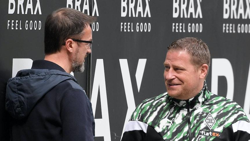 Gladbachs Manager Max Eberl (r.) unterhält sich am 17. April 2021 im Borussia-Park am Spielfeldrand mit Fredi Bobic (l.). Beide lächeln dabei.