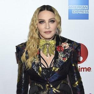 Madonna posiert im schwarzen Anzug mit auffälliger goldener Schleife um den Hals.