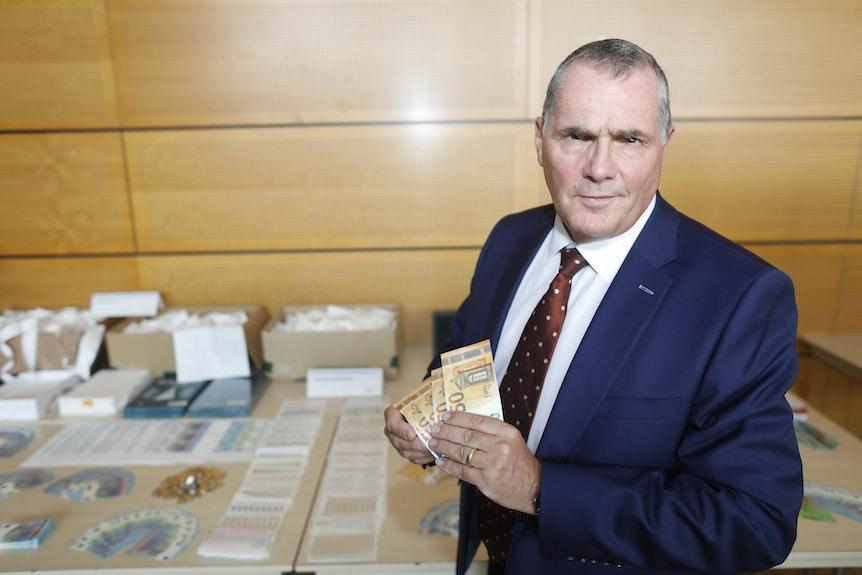 Klaus-Stephan Becker, Kölner Direktionsleiter Kriminalität, hält Falschgeld in der Hand.
