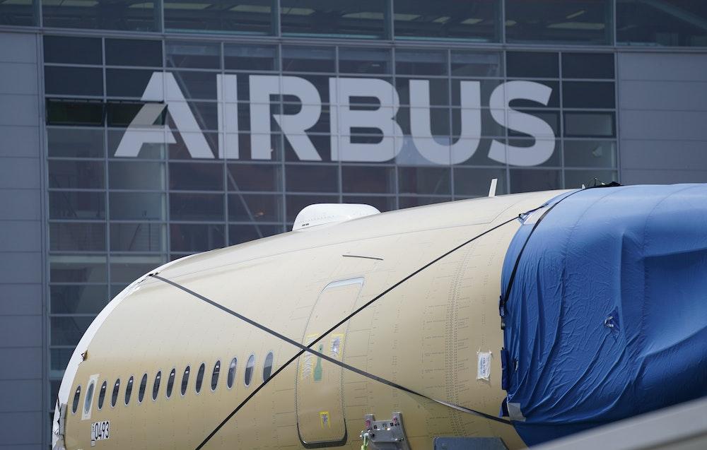 Ein Segment eines Flugzeugrumpfes eines Airbus A350 stehen vor einer Fertigungshalle auf dem Werksgelände des Flugzeugbauers Airbus.