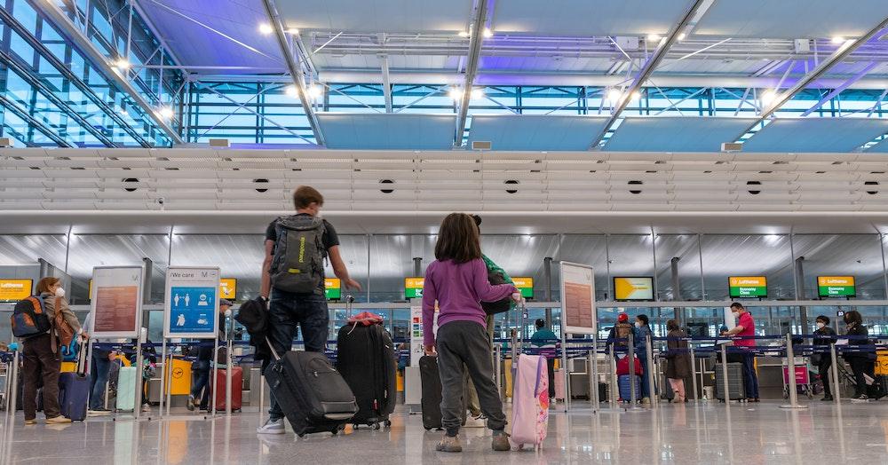Passagiere stehen am Flughafen München an einem Check-In-Schalter.