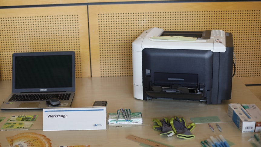 Auf einem Tisch stehen das Werkzeug der Falschgeld-Produzenten, ein normaler Drucker und ein Laptop.