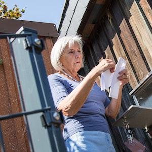 Eine ältere Dame steht am Briefkasten und sieht ihre Post durch. (Symbolfoto).