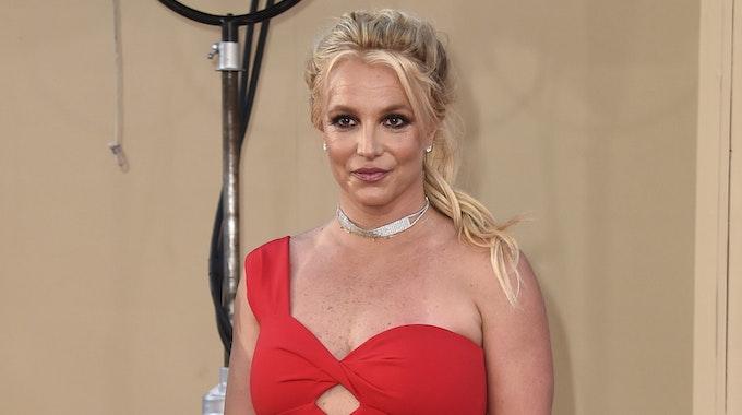 Britney Spears posiert im roten Kleid bei einer Veranstaltung.