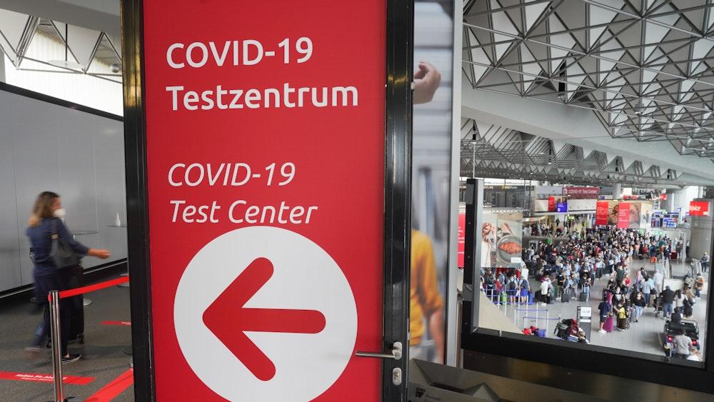 Zahlreiche Reisende stehen am Morgen an den Schaltern in einer der Abfertigungshallen des Frankfurter Flughafens (u.r.) während es links zum Covid-19-Testzentrum geht.
