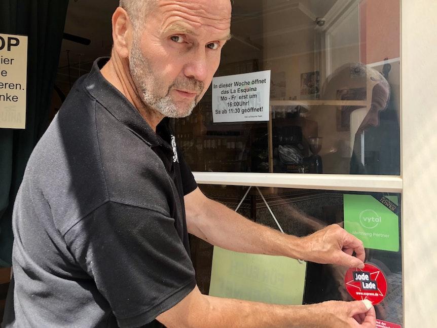 """Dieter Niehoff klebt den """"Jode Lade""""-Sticker an die Eingangstür der Tapas-Bar."""