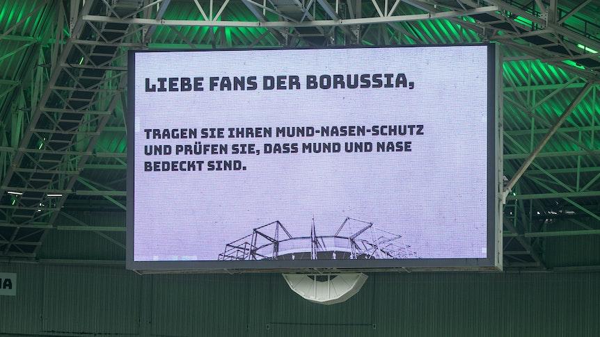 Im Gladbacher Borussia-Park, hier zu sehen am 26. September 2020, steigt am Samstag (31. Juli 2021) gegen den FC Groningen die Generalprobe für den Saisonstart. Bis zu 23.000 Fans dürfen trotz Coronapandemie dabei sein. Die Anzeigetafel im Stadion weist die Besucher darauf hin, dass sie ihren Mund-Nasen-Schutz tragen sollen.