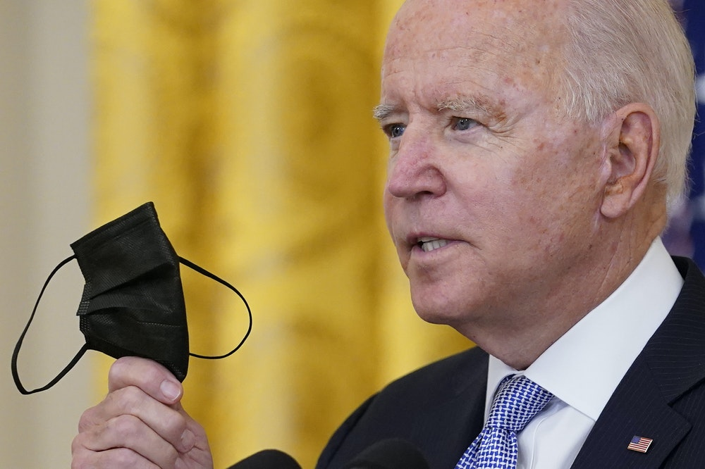Joe Biden, Präsident der USA (hier am 29. Juli 2021) hält seinen Mund-Nasen-Schutz während er im Weißen Haus in Washington über die Impfvorschriften für Bundesbedienstete spricht.