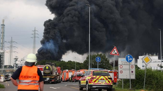Einsatzfahrzeuge der Feuerwehr stehen am 27. Juli unweit einer Zufahrt zum Chempark über dem eine dunkle Rauchwolke aufsteigt. Die Explosion löste einen Brand aus.