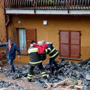Einsatzkräfte der Feuerwehr retten eine ältere Frau aus ihrem Haus in Laglio am Comer See.