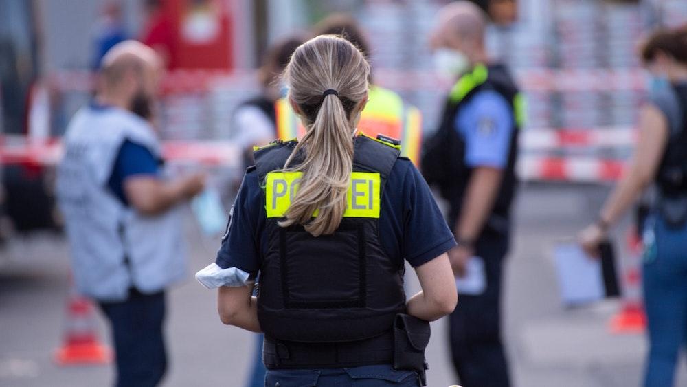 Polizisten stehen hinter Absperrbändern.