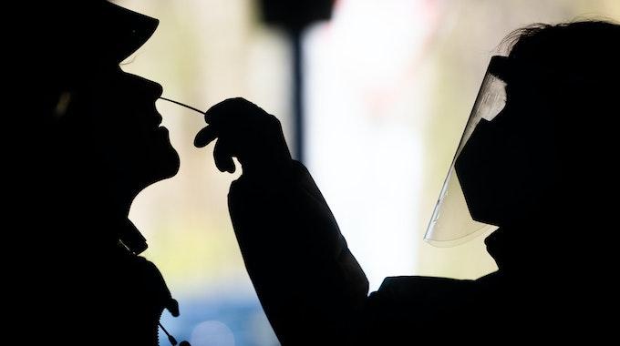 In einem Testzentrum nimmt eine Mitarbeiterin von einem Kunden einen Nasenabstrich.