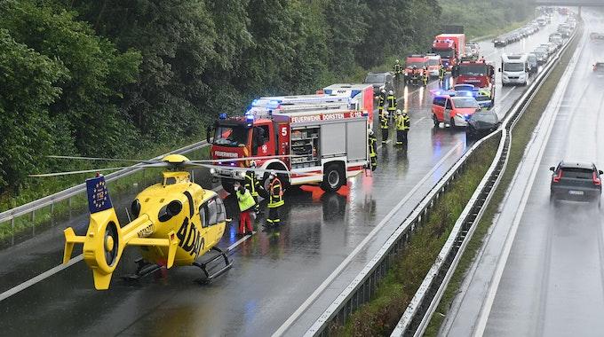 Einsatzkräfte der Feuerwegr und ein Hubschrauber des ADAC stehen auf der A31, wo sich zwei Unfälle ereignet haben.