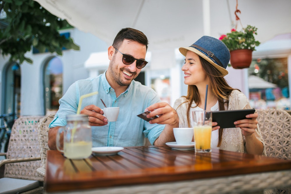 Beautiful couple having coffee on a date, using digital tablet and credit card for online shopping Foto aus Getty Datenbank