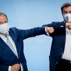 Armin Laschet und Markus Söder mit Ellenbogen-Gruß und Coronaschutzmaske.