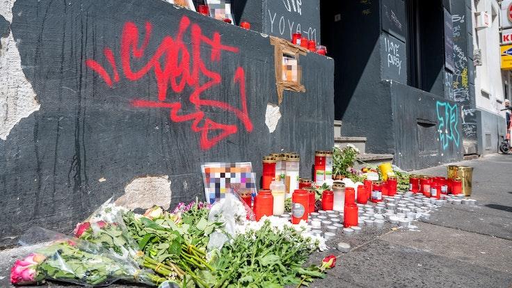 Blumen und Kerzen liegen am Tatort auf der Zülpicher Straße.