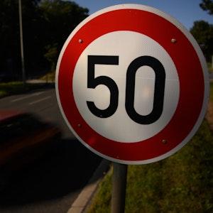 Ein Verkehrsschild zur Geschwindigkeitsbegrenzung auf Tempo 50 neben einer Straße