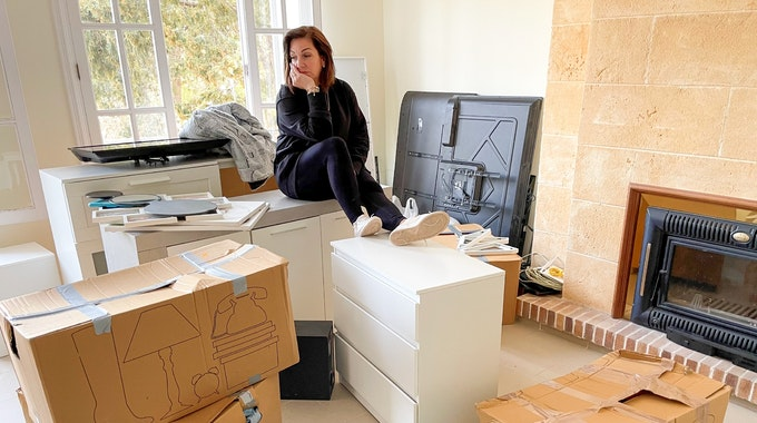 Danni Büchner sitzt auf ihren Umzugskartons, den Kopf hat sie auf die Hand gestützt.