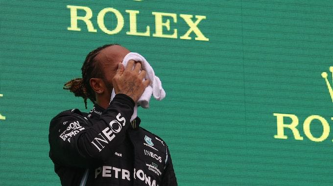 Formel 1: Lewis Hamilton wischt sich das Gesicht trocken auf dem Podium.