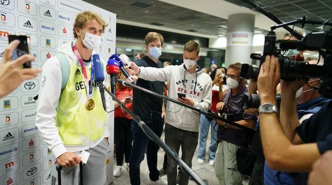 Der deutsche Tennisspieler Alexander Zverev spricht nach seiner Ankunft aus Tokio auf dem Frankfurter Flughafen mit Medienvertretern.