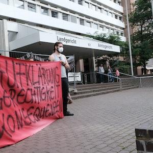 Demonstranten halten ein Plakat vor dem Kölner Landgericht hoch.