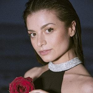 """""""Bachelorette"""" Maxim Herbord am Strand. Sie hält eine Rose in der Hand."""