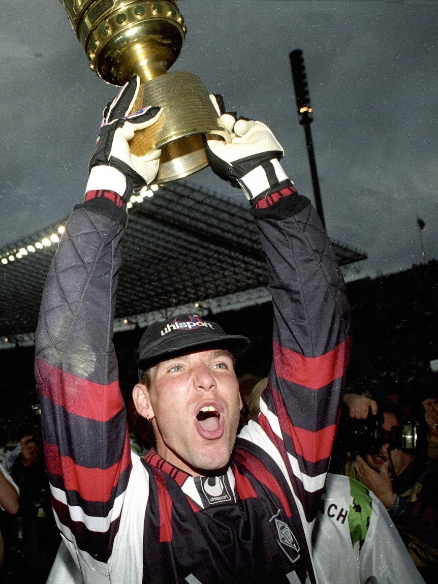 Torhüter Uwe Kamps bejubelt am 24. Juni 1995 den Pokalgewinn mit Borussia Mönchengladbach. Er hält den Pokal in den Armen und schreibt seine Freude herraus.