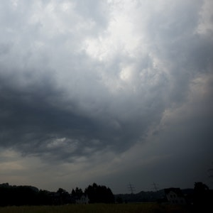 Dunkle Gewitterwolken ziehen über ein Feld in Hattingen (Nordrhein-Westfalen).