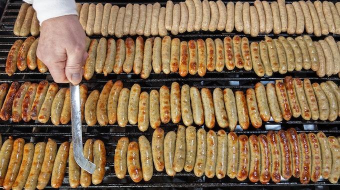 Nürnberger Rostbratwürste liegen an einem Stand auf dem Nürnberger Christkindlesmarkt auf einem Grill.