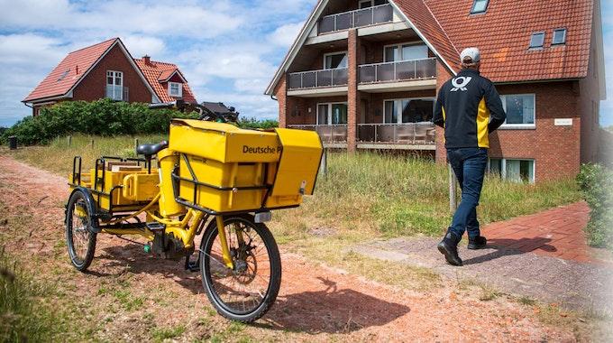 Ein Postbote bringt Post zu einem Haus auf Baltrum.
