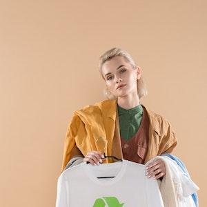 Eine junge blonde Frau hält einige Kleidungsstücke in der Hand.