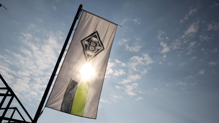 Die Vereinsfahne von Borussia Mönchengladbach weht vor der Sonne.