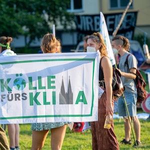 """Eine Aktivistin hält bei einer Demonstration die """"Kölle fürs Klima""""-Flagge nach oben."""