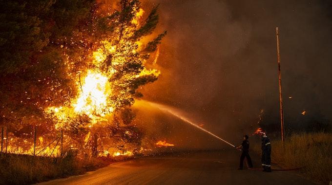 Feuerwehrleute bekämpfen am 05.08.2021 einen Waldbrand in einem Waldgebiet nördlich von Athen.
